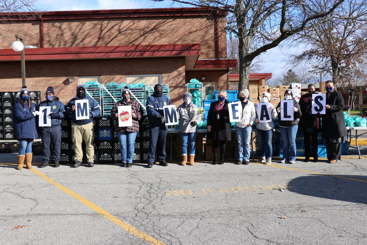 Vails Gate STEAM Academy Meal Distribution team celebrates 1 Million Meals with signs and a group photo.