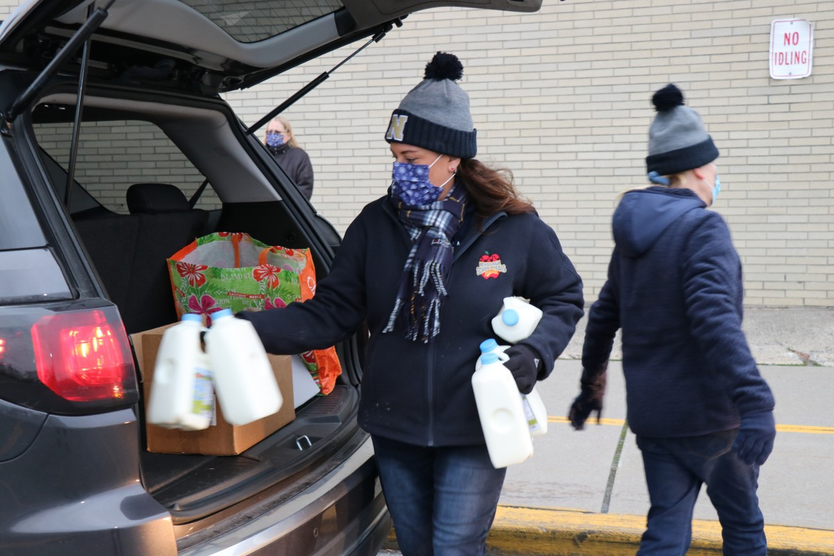 Member of the food services team distributes milk to a car.