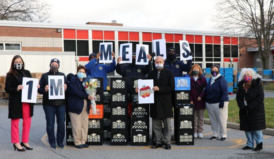 GAMS Meal Distribution team celebrates 1 Million Meals with signs and a group photo.