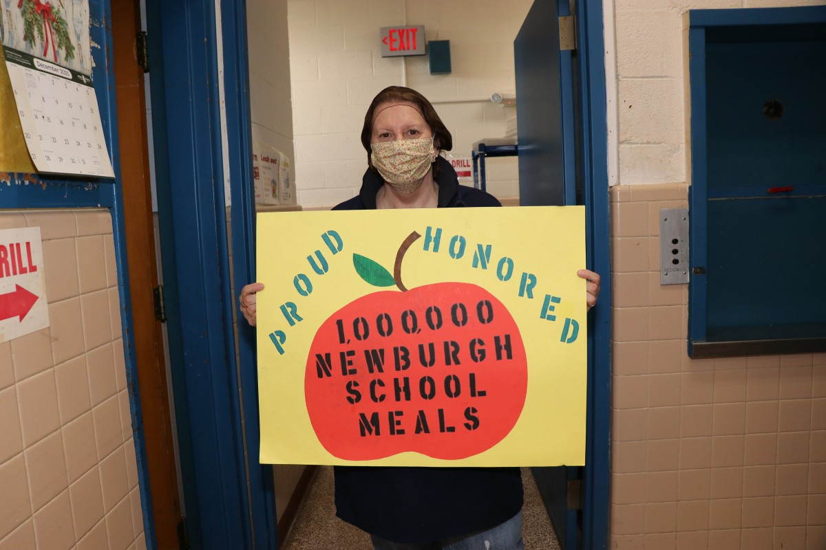 Cafeteria manager holds up celebratory sign.