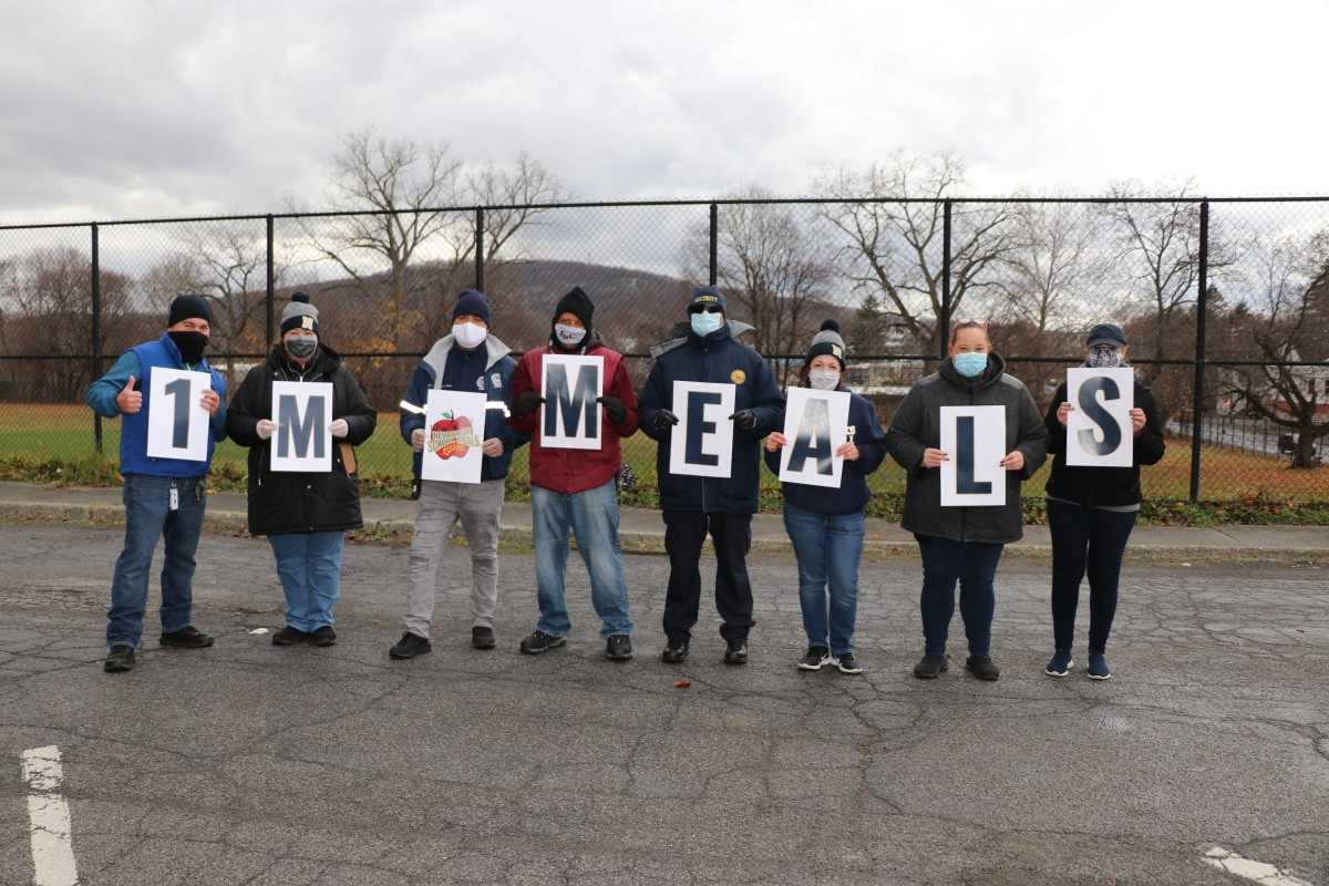 South Middle School Meal Distribution team celebrates 1 Million Meals with signs and a group photo.