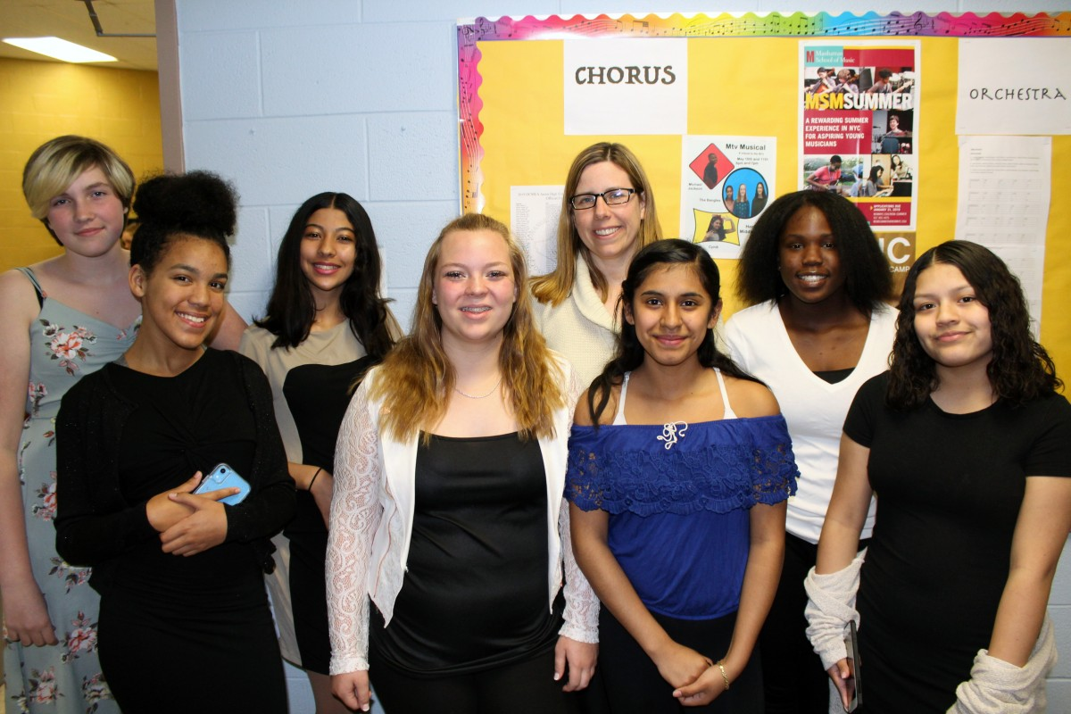 The 8th Grade Chorus Members. (From L to R) Front Row: Visella De la Cruz, Kamryn Betcher, Brianna Garcia, Arieth Valenzuela. (From L to R) Back Row: Sabrina Hope, Yosr Haggui, Ms. Clina, and Katayshia Rogers. Missing at the time of the photo Auriel Rosemberg.