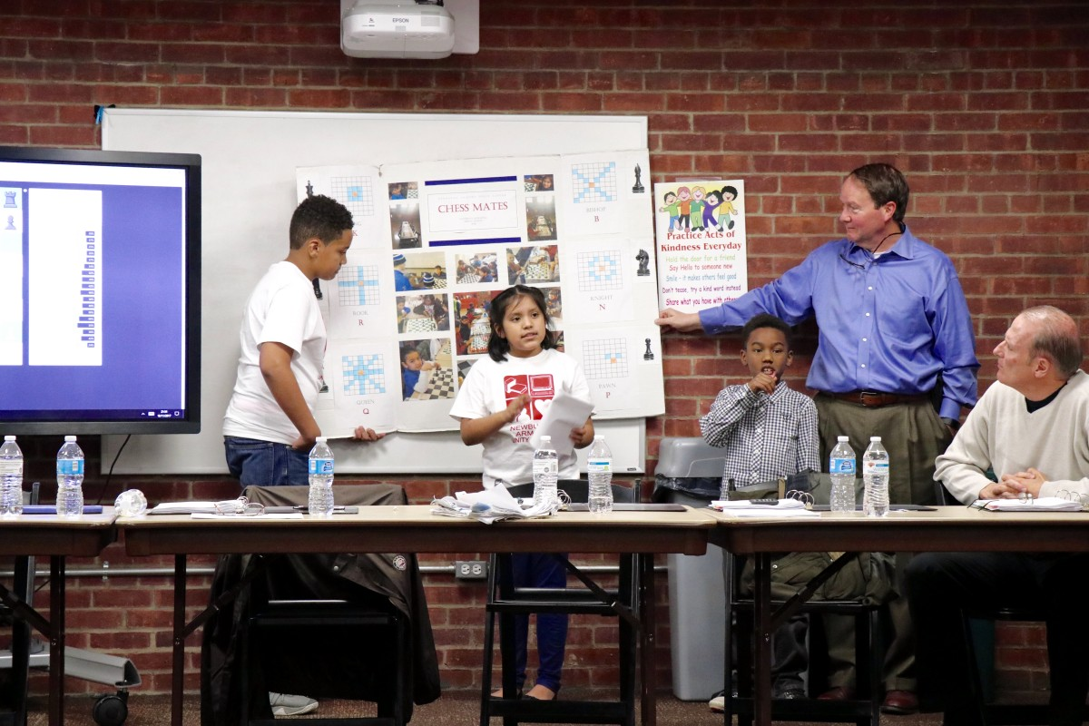 4th grade Isabella explains the game of chess to Armory Board members