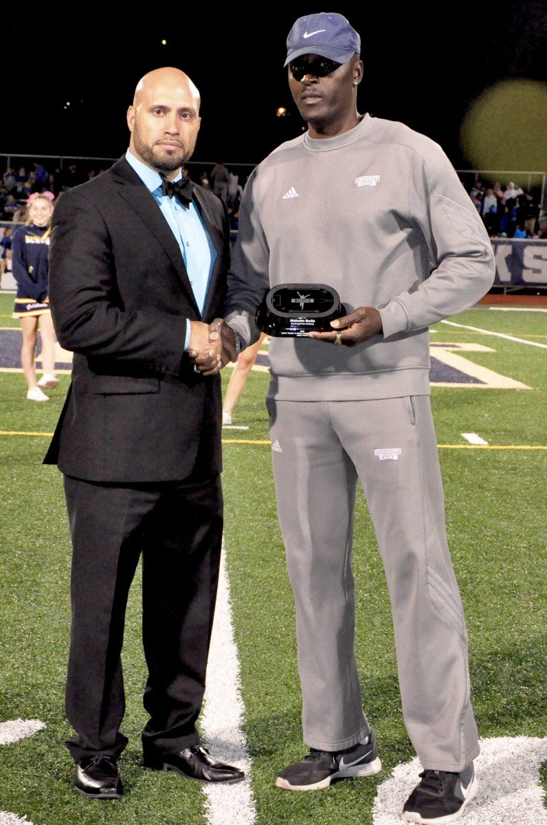 Coach Malcolm Burks honored as Boy's Track and Field Coach of the Year at a football game. Pictured with Dr. Padilla, Superintendent of Schools