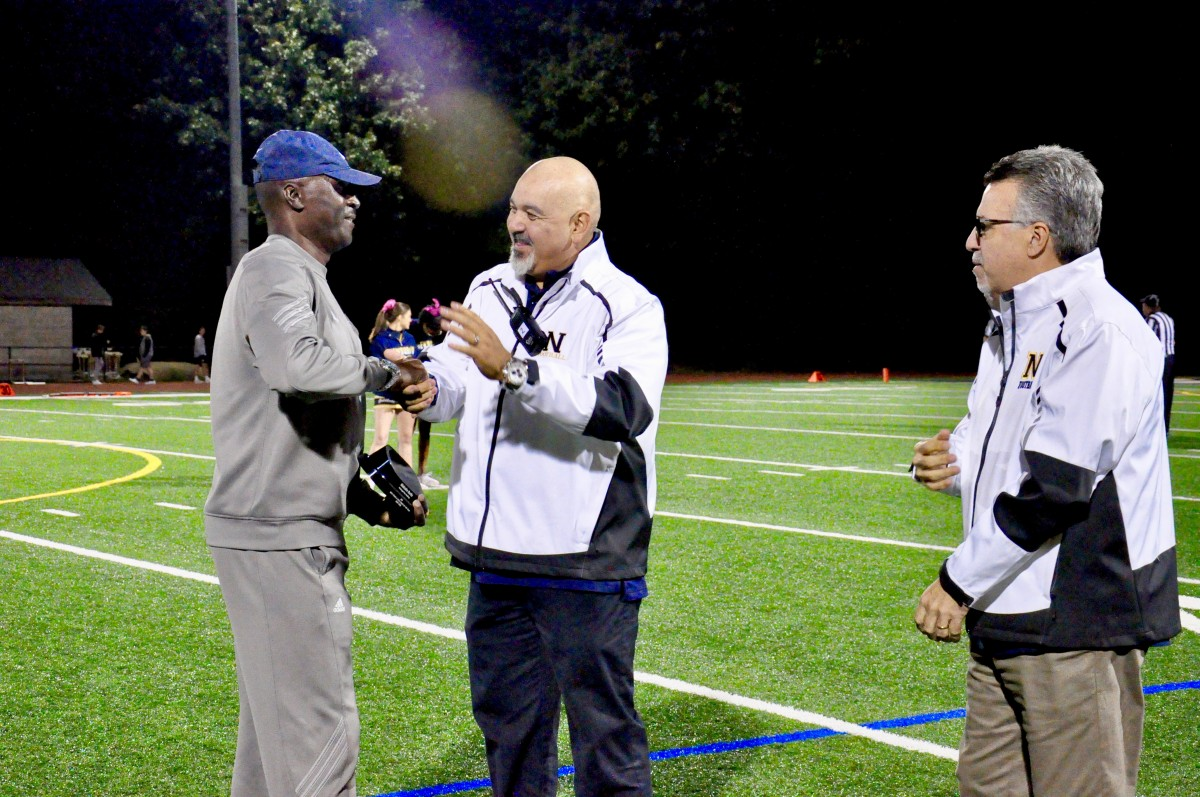 Coach Malcolm Burks honored as Boy's Track and Field Coach of the Year at a football game. Pictured with Principals Rodriguez and Doddo.