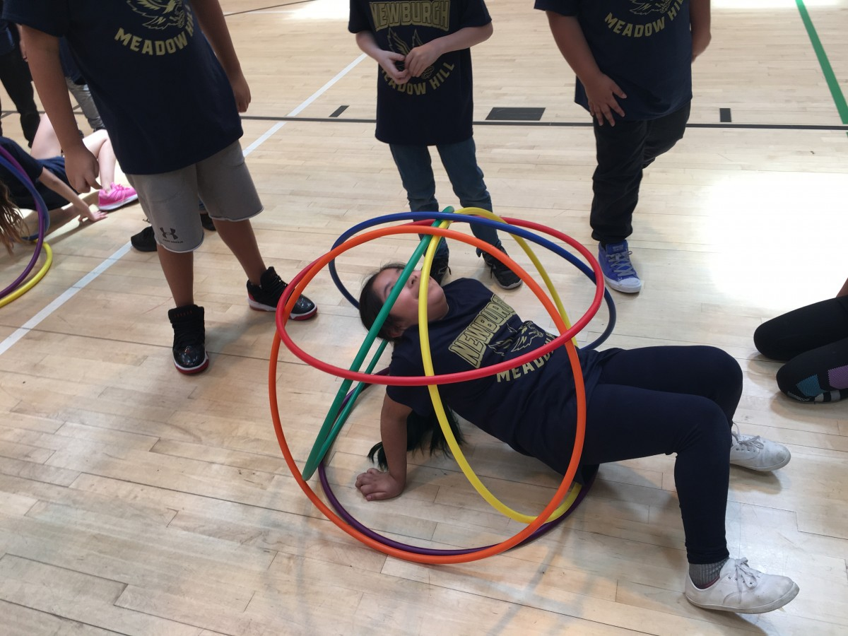 Students participate in activity with hoops.