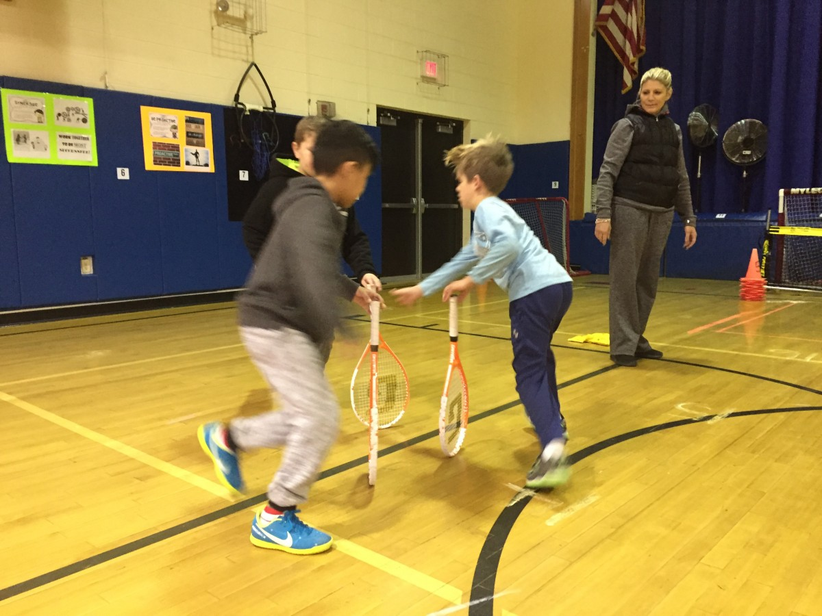 Students practice tennis skills as part of the program.