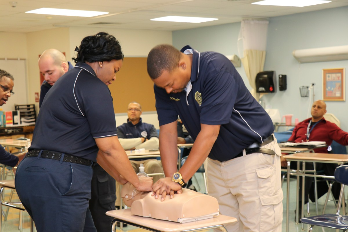 Security guards practicing proper form for basic life Basic Life Support (BLS) CPR.