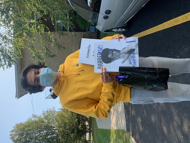 Student poses with a picture holding their supplies.