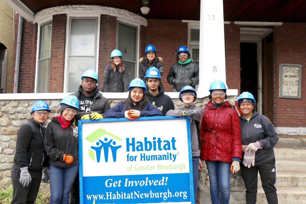 Students pose in front of house and Habitat sign