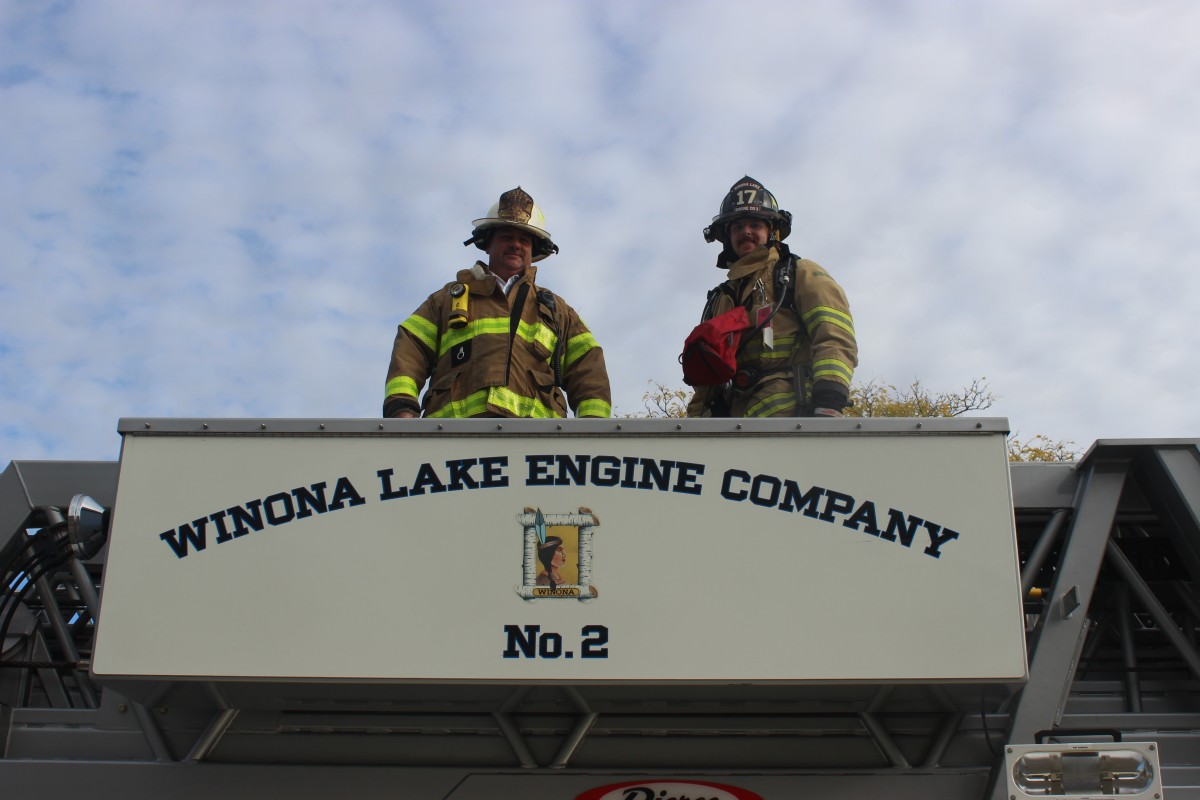 Firefighters pose on top of their truck.
