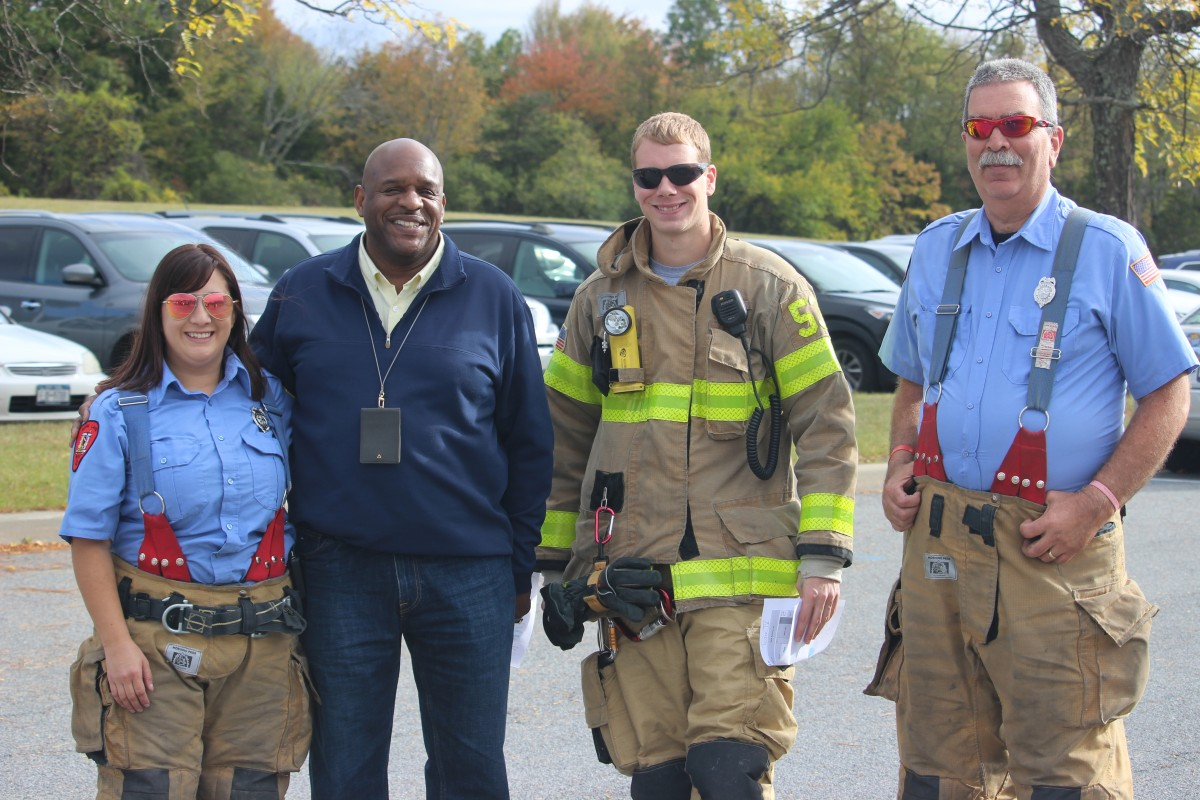 Firefighters pose with assistant principal Mr. Armand.