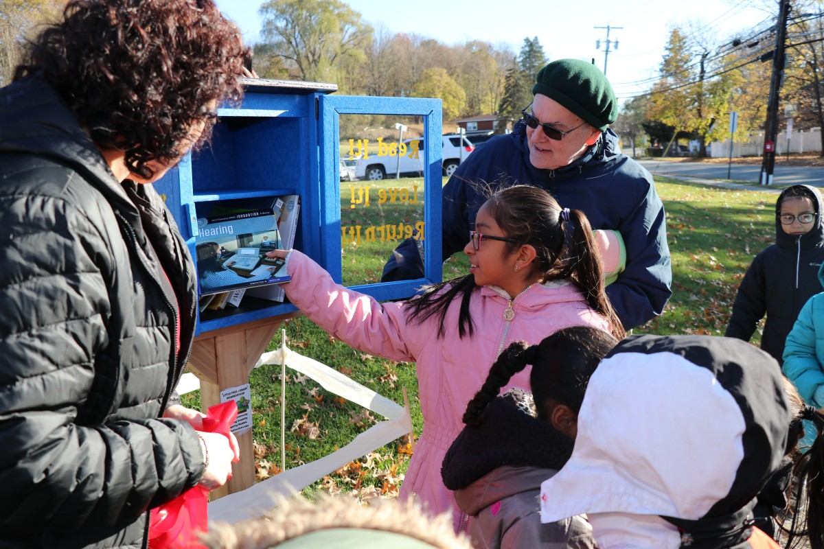 Students placing books in the outdoor lending library box.