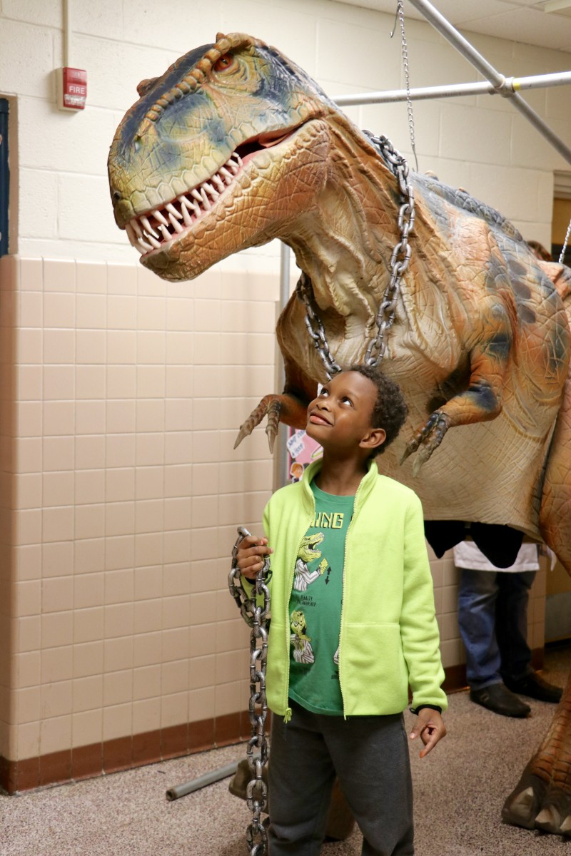 Student poses with Fluffy the T-Rex