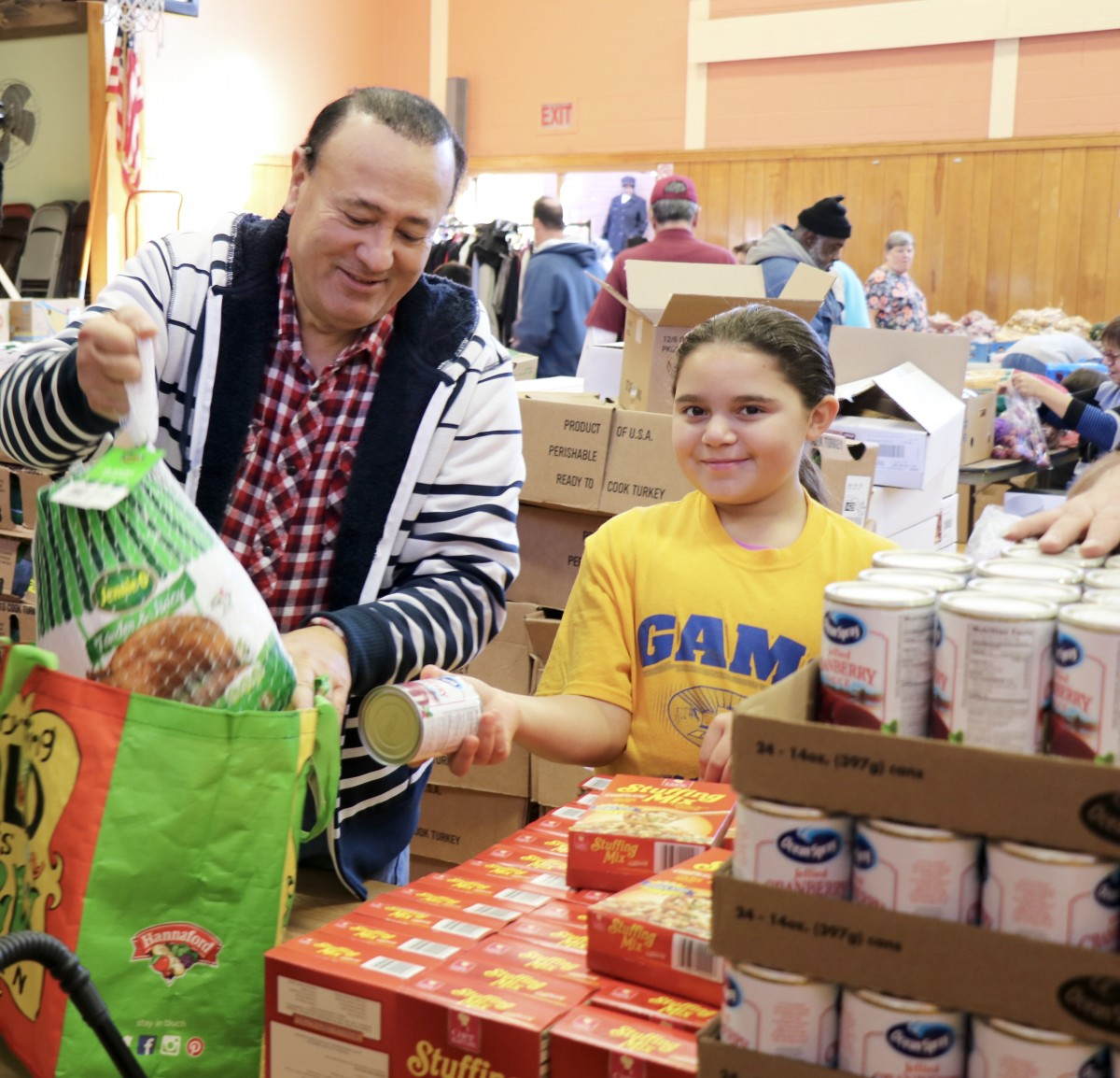 Student distributes food with Assemblyman Skartados