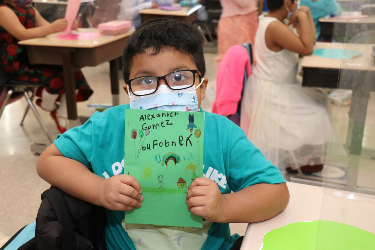 Scholar holding up the book that they wrote, illustrated, published, and read.