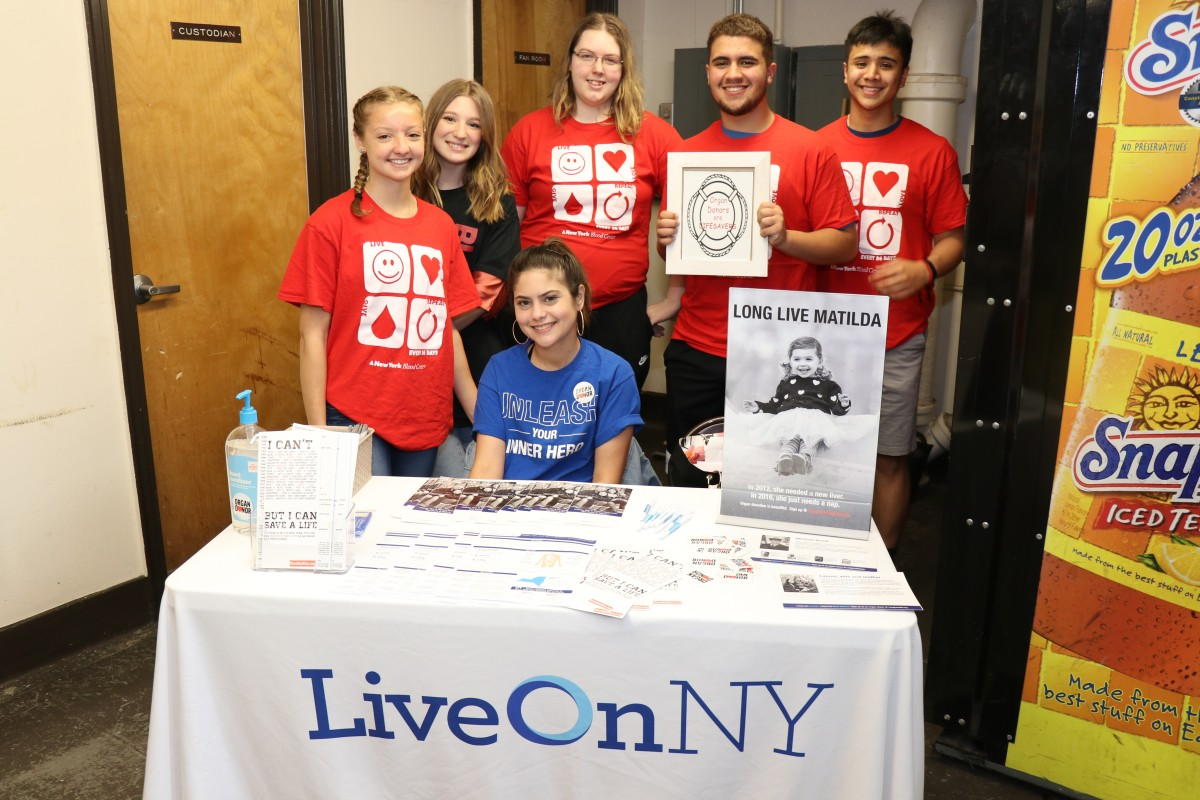 Students pose at organ donor table.