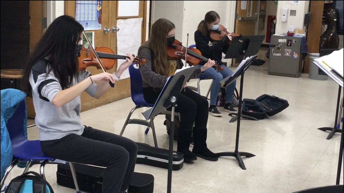 Students playing their string instruments.
