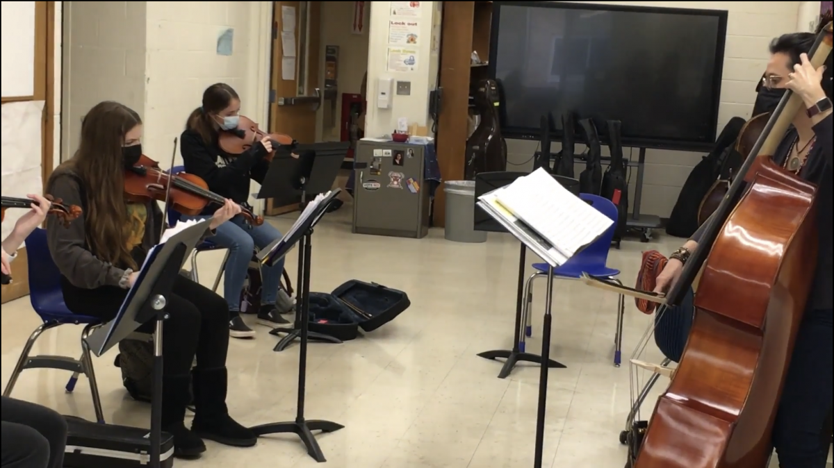 Students play their string instruments with their teacher, Ms. Monica Monica Antonelli-Guido.