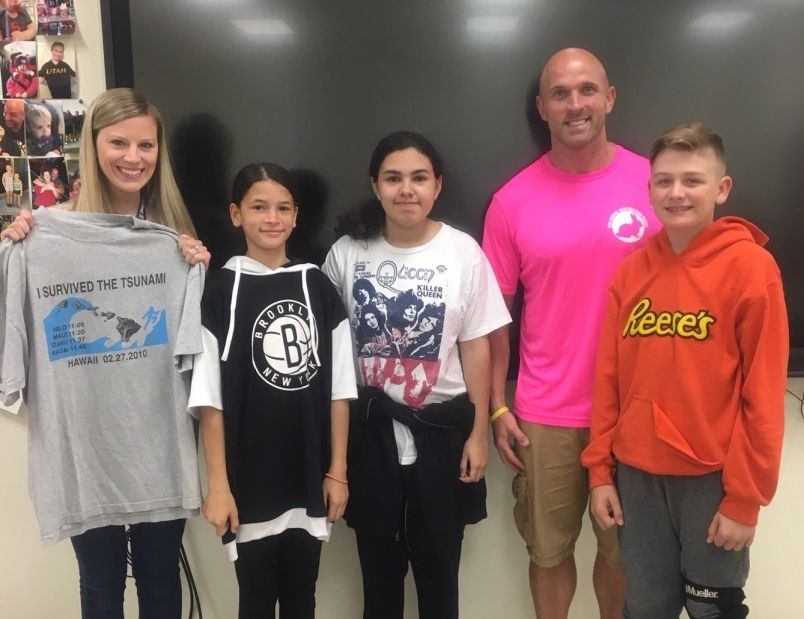 Students stand with Mr. Olsen and their t-shirt.