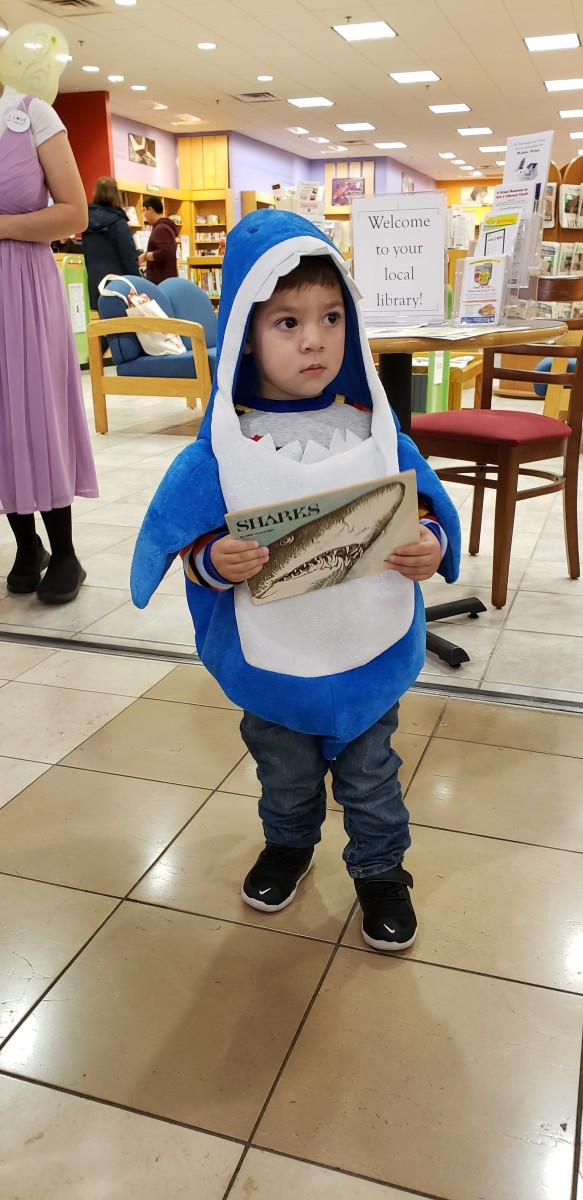 Child in costume holds a book.
