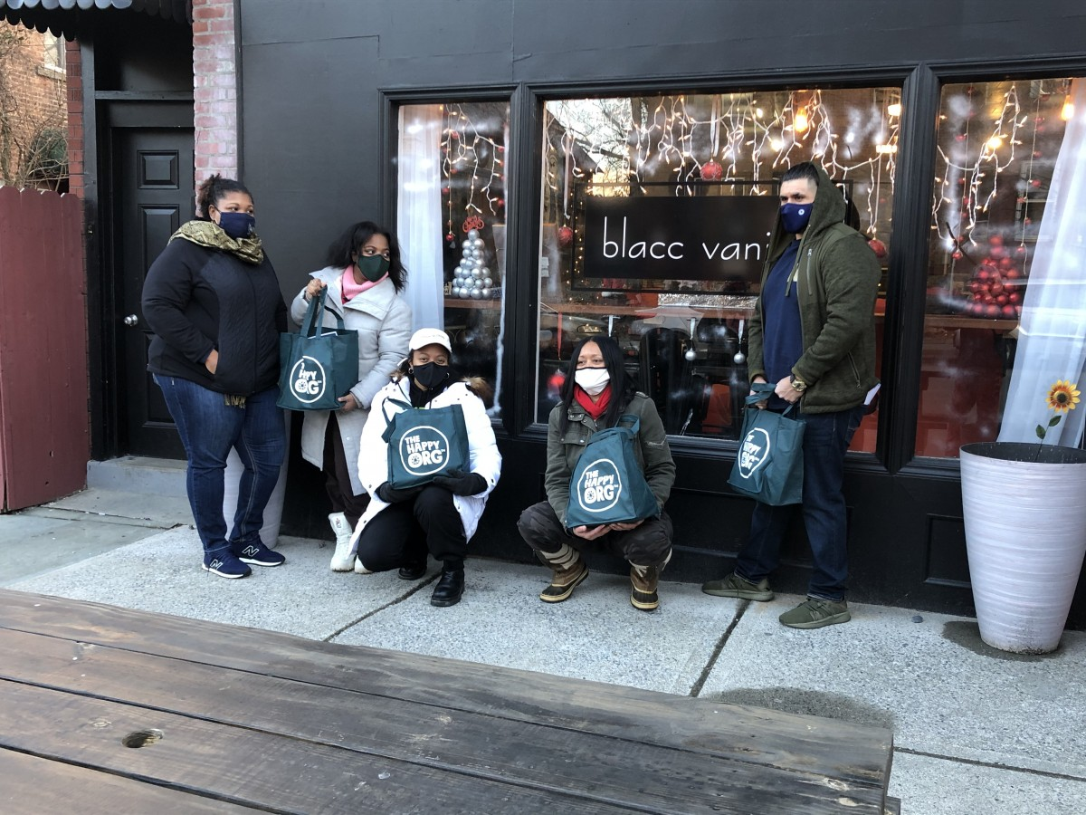 Group of community members with their bags of goods.