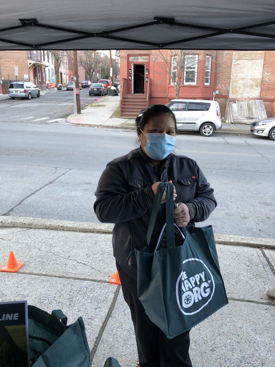 Community member poses for a photo holding their bag.