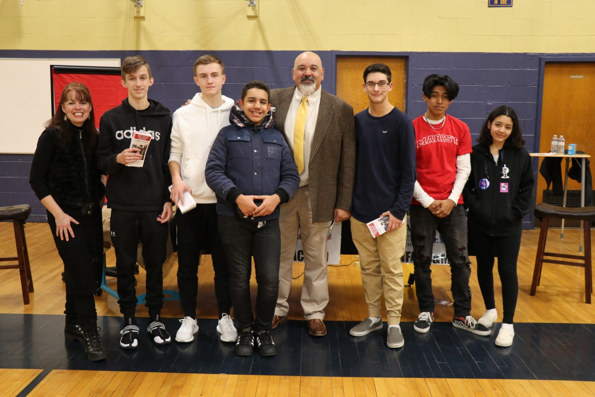 Scholars pose for a  photo with building principal Mr. Raul Rodriguez.