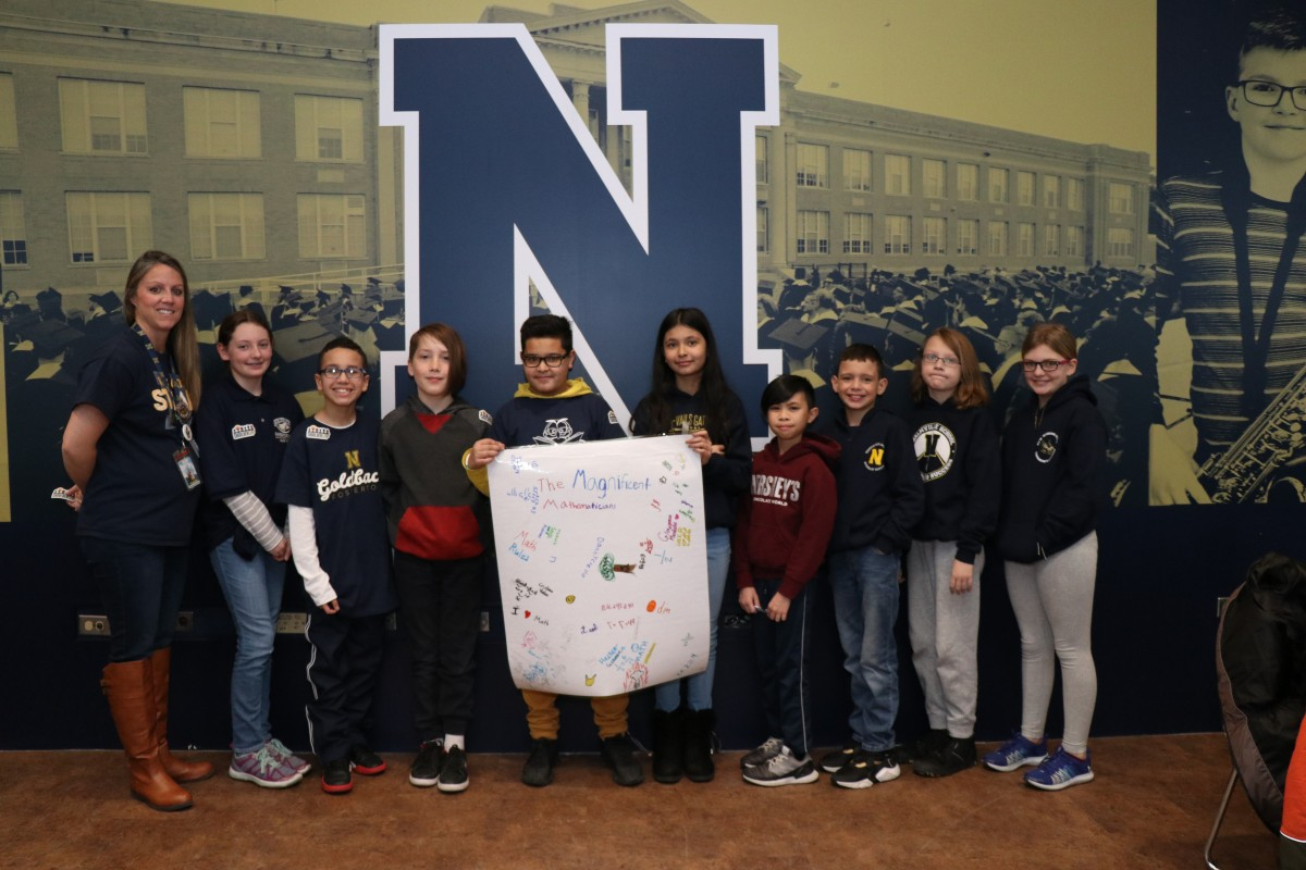 Scholars pose for a photo with their team.
