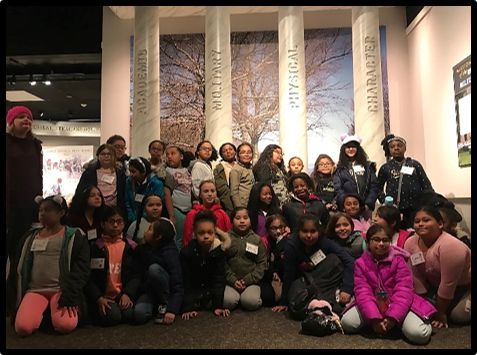 4th and 5th grade girls standing with the USMA Pillars at the Visitor's Center
