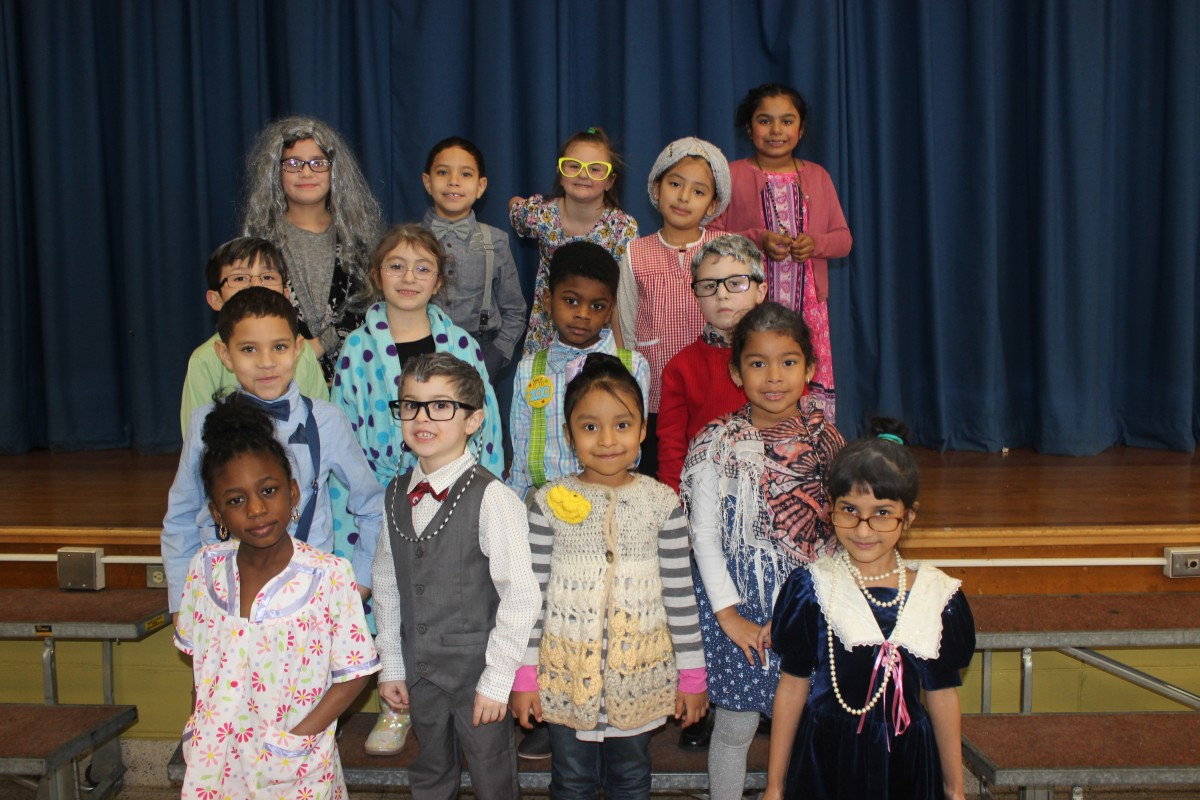 Students pose for a photo wearing costumes of a 100 year old.