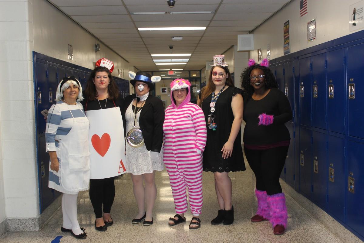 Teachers pose in their Alice in Wonderland costumes.