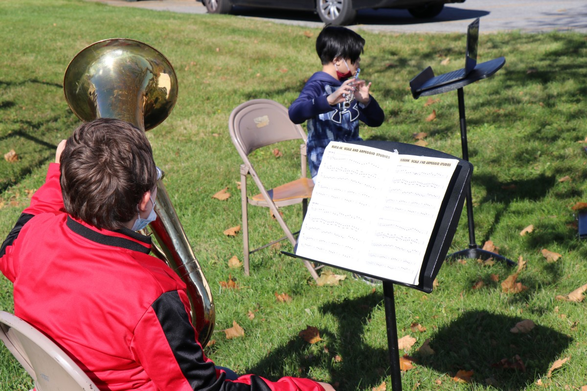 Student playing instrument outside.