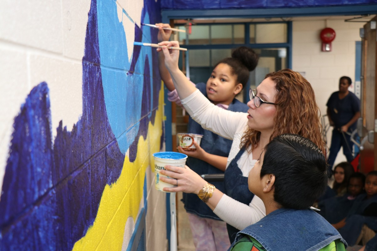 Teacher Mrs. Williams teaching students how to paint the mural.