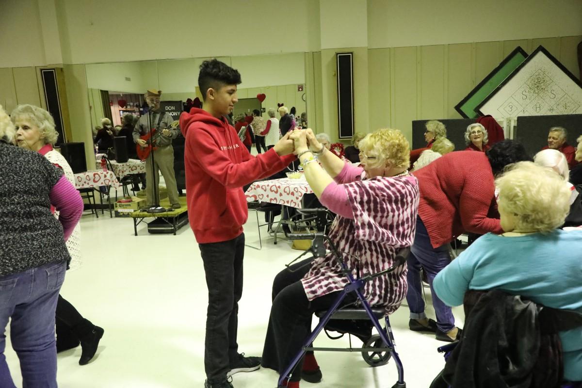 Student dances with a senior guest.