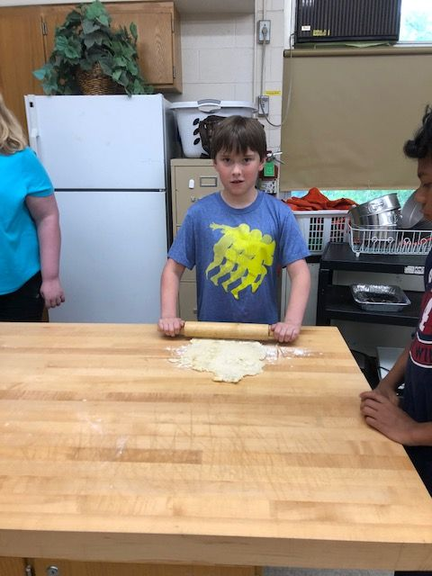 Student rolling pizza dough.