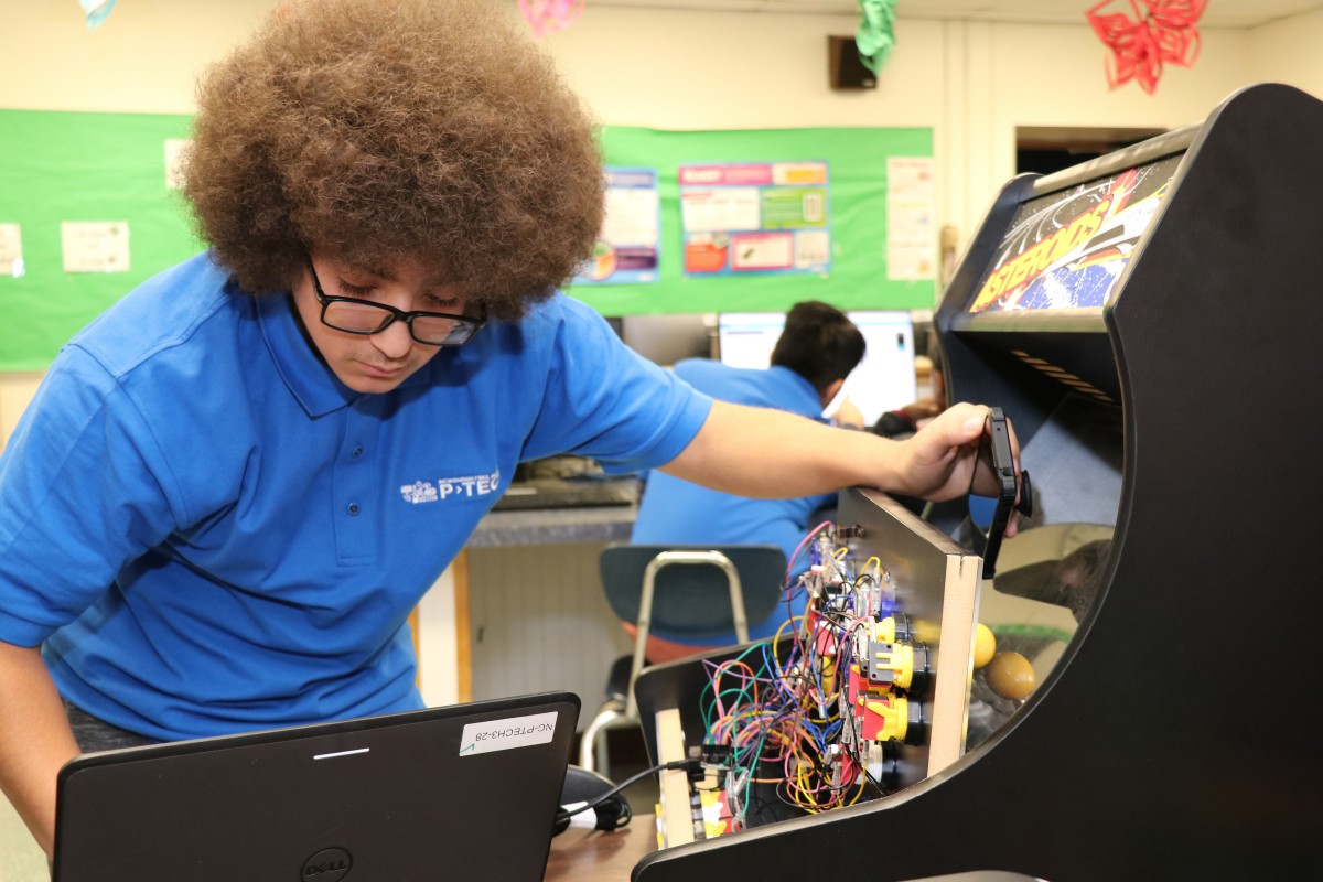 High school scholar works on video game coding project.