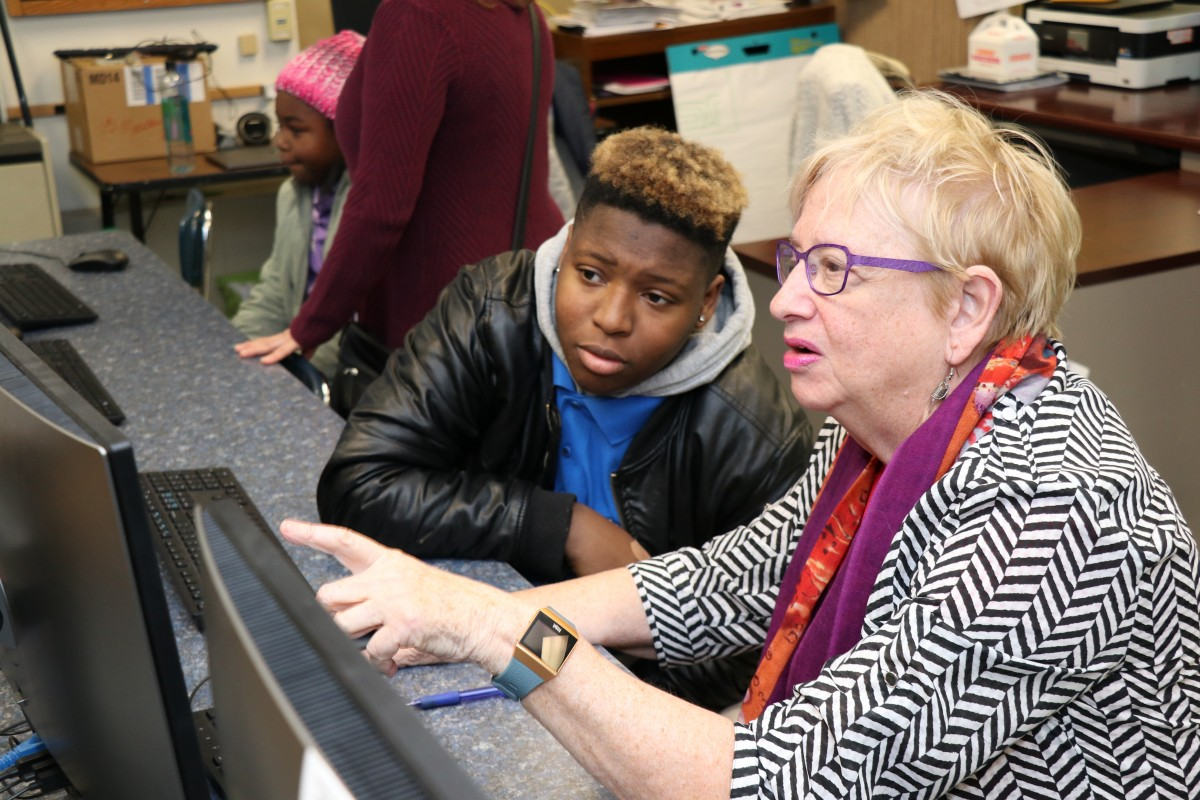 High school scholar helps community member with coding activity.