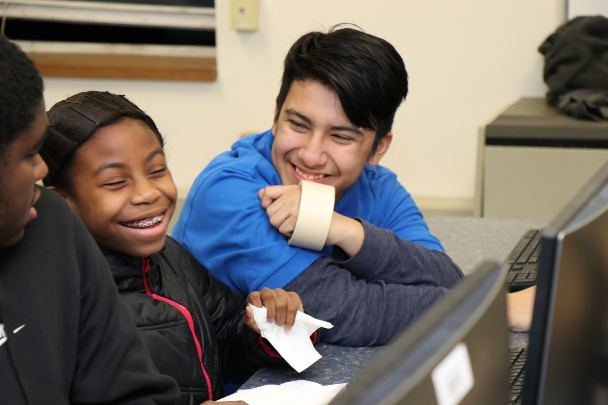 High school scholar helps younger student with coding activity.