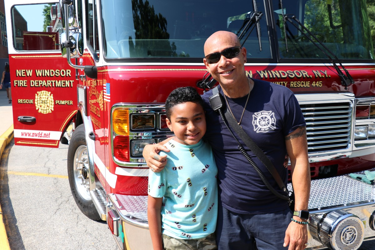 Student poses with firefighter.