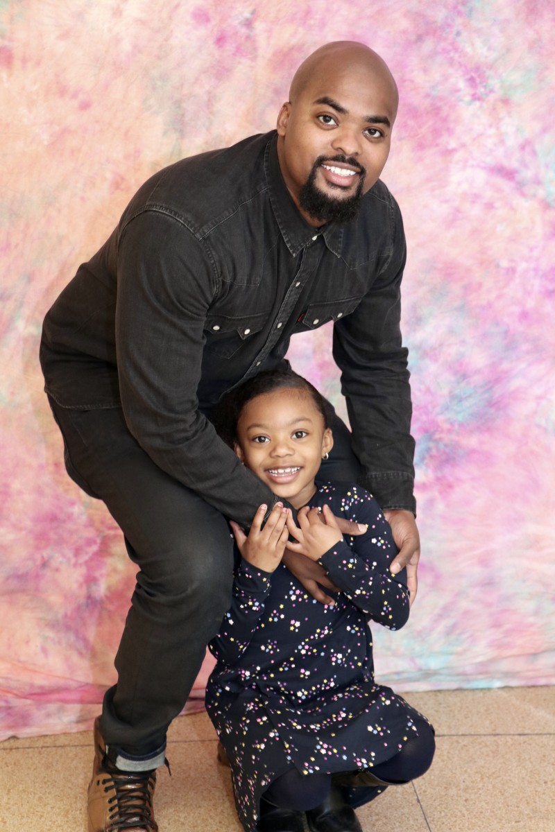 School Counselor, Mr. Kareem Donaldson poses with his daughter at the photo booth