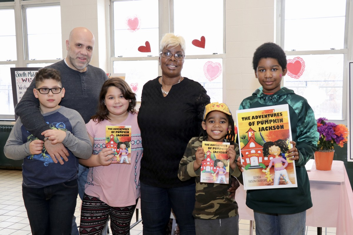 Author, Ms. Glenda Faison-Crawford poses with students holding her book