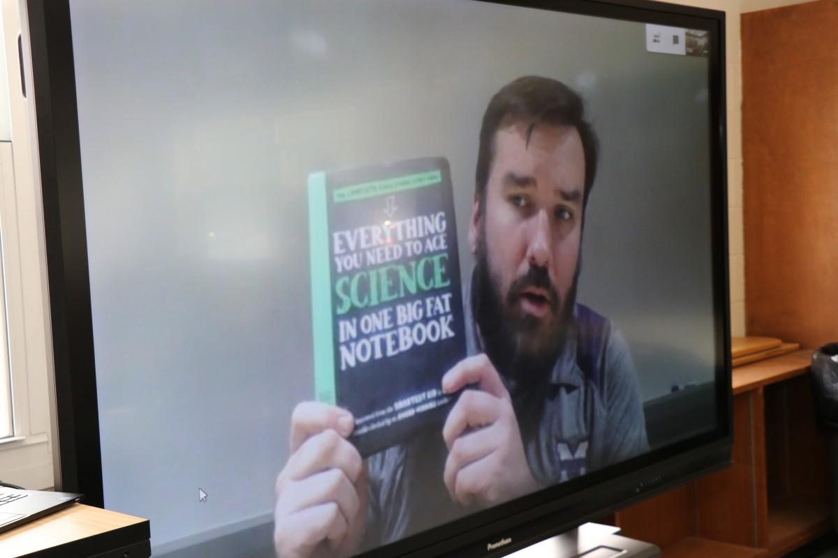 Presenter shows new textbook.