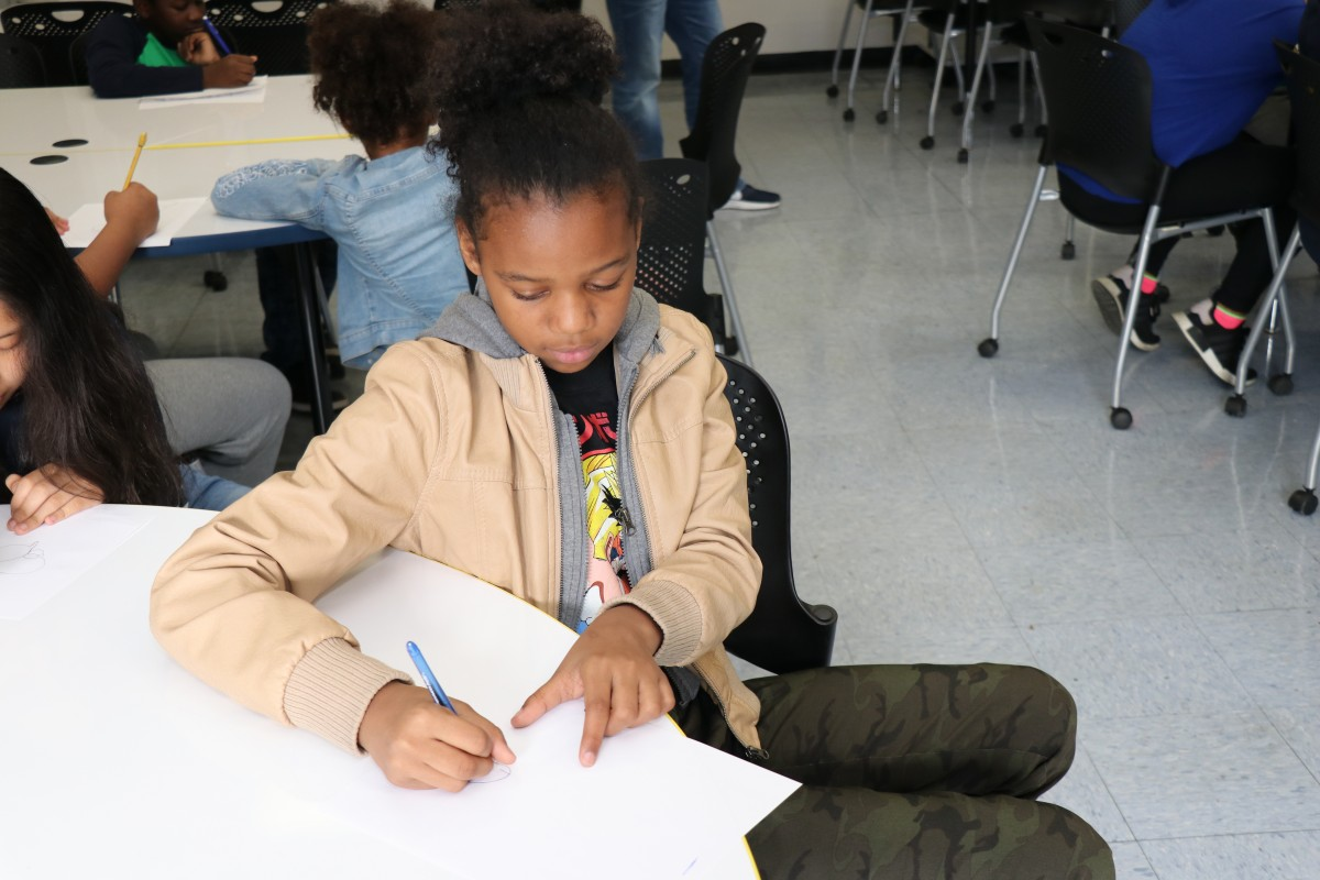 Students try drawing characters using a handful of shapes, under the direction of the presenter.