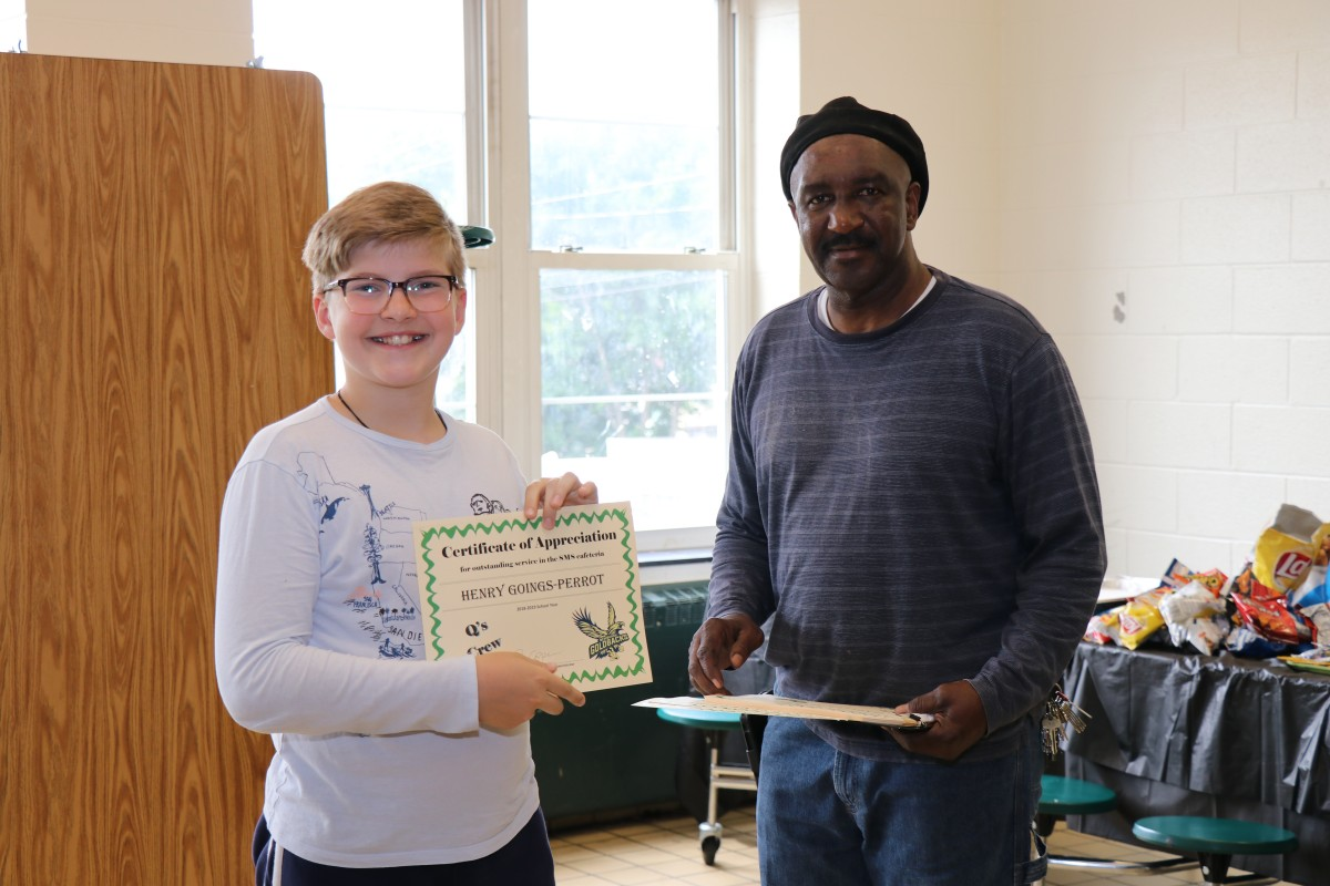 Student receives certificate from Mr. Q.