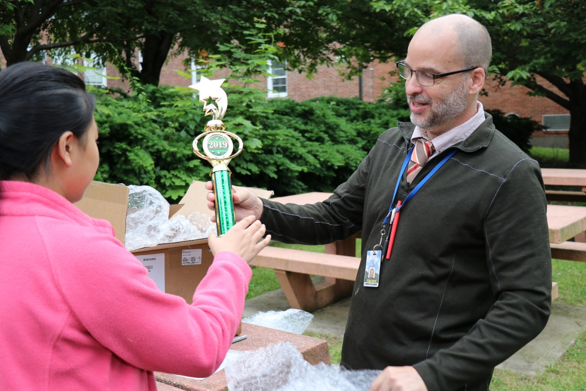 Mr. Hickey hands a trophy to a student.