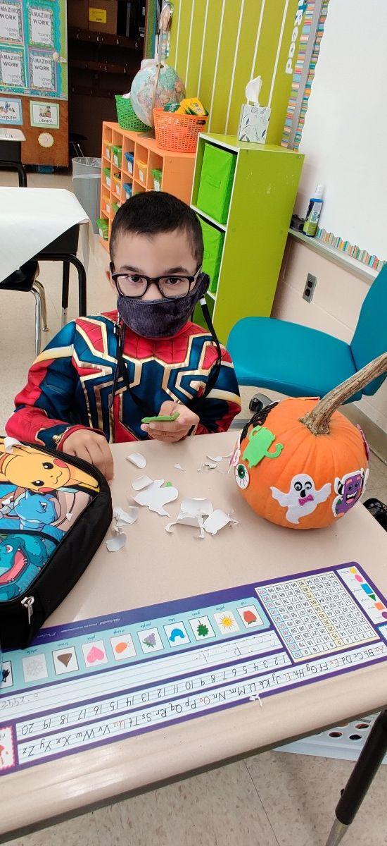 Students decorating pumpkins in classroom.