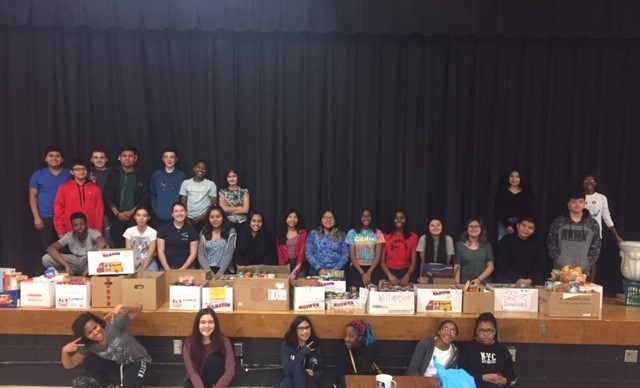 Students sit on stage with donations.