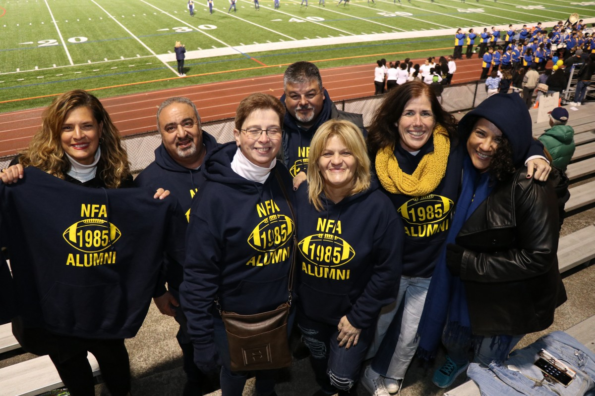Members of the class of 1985 pose with their sweatshirts.