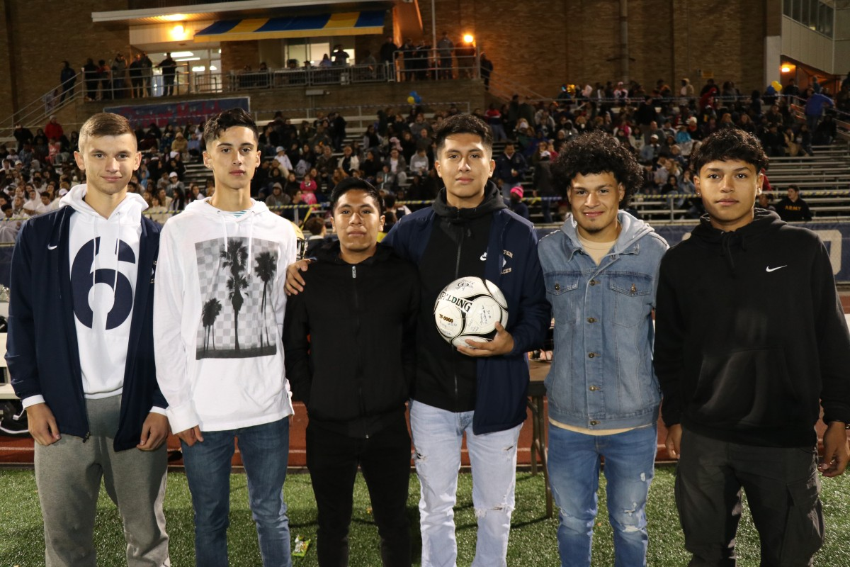 Athletes stand with the signed ball.